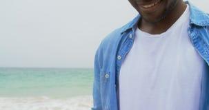 Opinião lateral o homem afro-americano que usa o telefone celular na praia 4k vídeos de arquivo