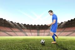 Opinião lateral o homem asiático do jogador de futebol que retrocede a bola Foto de Stock Royalty Free