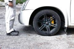 A opinião lateral o homem automotivo do mecânico na chave guardando uniforme branca no seu entrega pronto a reparar o motor de au foto de stock