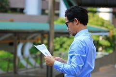 Opinião lateral o homem de negócio asiático novo seguro que olha cartas ou documento e que pensa o seu trabalho no fundo urbano d Imagem de Stock