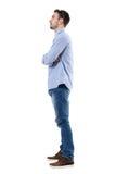 Opinião lateral o homem de negócios novo com os braços cruzados que olham afastado Fotografia de Stock Royalty Free
