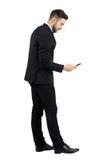 Opinião lateral o homem de negócios novo na mensagem de datilografia do terno no écran sensível do smartphone Imagem de Stock