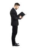 Opinião lateral o homem de negócios novo no contrato de assinatura do terno Imagens de Stock