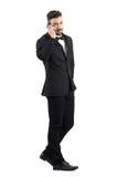 Opinião lateral o homem de negócios novo no terno que anda e que fala no telefone celular que gira principal para a câmera Fotos de Stock