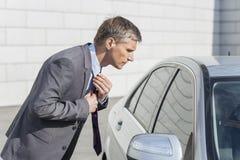 Opinião lateral o homem de negócios que ajusta o laço ao olhar na janela de carro Foto de Stock