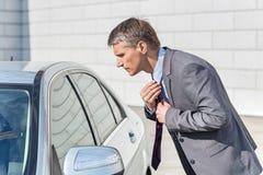 Opinião lateral o homem de negócios que ajusta o laço ao olhar na janela de carro Fotografia de Stock