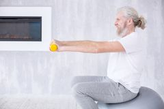 Opinião lateral o homem idoso que exercita com pesos na bola da aptidão fotografia de stock