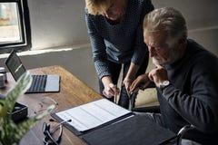 Opinião lateral o homem idoso que senta-se na cadeira de rodas que olha o formulário do contrato de seguro da vida foto de stock royalty free