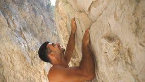 Opinião lateral o homem muscular novo que escala na rocha Indivíduo forte que ascensão no pico da rocha que faz grandes esforços  filme