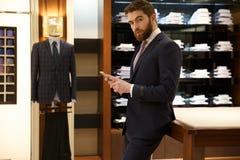 Opinião lateral o homem no terno que guarda o smartphone Fotos de Stock Royalty Free