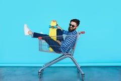 Opinião lateral o homem novo alegre que senta-se no carrinho de compras imagens de stock royalty free