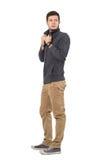 Opinião lateral o homem novo ocasional que ajusta o olhar do colar da camiseta atrás Imagem de Stock