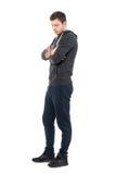 Opinião lateral o homem novo triste na roupa desportivo que olha para baixo com braços cruzados Fotografia de Stock Royalty Free