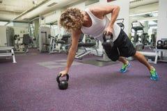Opinião lateral o homem que exercita com os sinos da chaleira no gym Fotografia de Stock