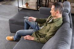 opinião lateral o homem que olha a tevê ao descansar no sofá fotografia de stock royalty free