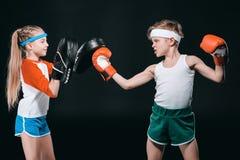 Opinião lateral o menino e a menina no encaixotamento do sportswear isolados no preto fotografia de stock