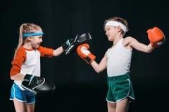 Opinião lateral o menino e a menina no encaixotamento do sportswear isolados no preto imagem de stock royalty free
