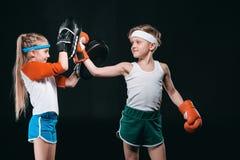 Opinião lateral o menino e a menina no encaixotamento do sportswear isolados no preto fotos de stock