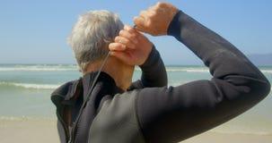 Opinião lateral o surfista masculino caucasiano superior ativo que veste o terno molhado na praia 4k video estoque