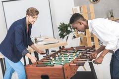 opinião lateral os homens de negócios multiculturais que jogam o futebol da tabela junto ao descansar fotos de stock royalty free