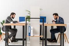 opinião lateral os homens de negócios que trabalham e que bebem o café imagens de stock royalty free