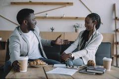 opinião lateral os sócios comerciais afro-americanos que têm a conversação na tabela imagens de stock royalty free