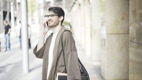 Opinião lateral um homem de negócios considerável que fala seu telefone esperto na rua e que olha a câmera Imagens de Stock