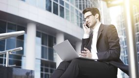 Opinião lateral um homem de negócios novo considerável que trabalha com um portátil exterior seu escritório Fotos de Stock