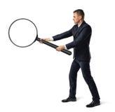 Opinião lateral um homem de negócios que guarda a lente de aumento grande com ambas as mãos isoladas no fundo branco imagem de stock royalty free