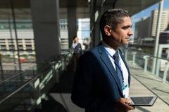 Opinião lateral um homem de negócios que guarda uma tabuleta digital e que olha afastado durante todo janelas foto de stock