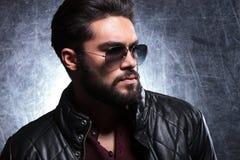 Opinião lateral um homem novo com a barba longa nos óculos de sol Fotos de Stock