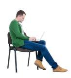 Opinião lateral um homem que senta-se em uma cadeira para estudar com um portátil imagens de stock royalty free
