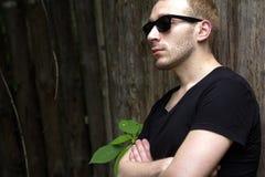 Opinião lateral um indivíduo nos óculos de sol pela cerca Imagem de Stock