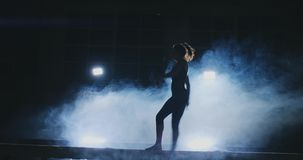 Opinião lateral uma ginasta fêmea que faz pino rachado no feixe de equilíbrio contra o fundo preto video estoque
