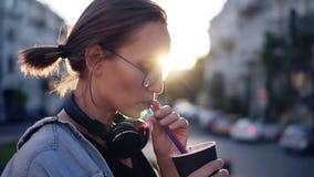 Opinião lateral uma jovem mulher bonita com os fones de ouvido em sua bebida bebendo do pescoço usando uma palha Menina loura no vídeos de arquivo