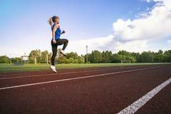 Opinião lateral uma jovem mulher do ajuste que movimenta-se no estádio Um atleta novo corre no sportswear no estádio no adiantado fotografia de stock