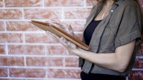 Opinião lateral uma jovem mulher que usa a tabuleta digital, Foto de Stock