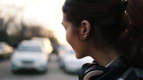 Opinião lateral uma menina com os fones de ouvido em torno de seu pescoço Sorri, gerencie para o olhar em uma perspectiva borrada filme