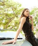 Mulher de negócios que inclina-se no carro com telefone. fotografia de stock royalty free