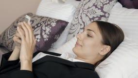 Opinião lateral uma mulher de negócios que texting no telefone em uma sala de hotel durante uma viagem de negócios video estoque
