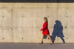 Opinião lateral uma mulher elegante que veste o revestimento vermelho, saia e guardando uma bolsa branca ao andar na rua em um di foto de stock royalty free