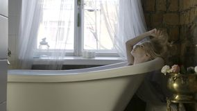 Opinião lateral uma mulher loura nova bonita que relaxa no interior do banheiro e que toca em seu cabelo a??o Um assento da menin video estoque