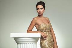 Opinião lateral uma mulher no vestido que inclina-se na coluna foto de stock royalty free