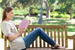 Opinião lateral uma mulher que lê uma novela em um banco de parque foto de stock royalty free