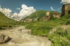 Opinião longa da exposição da vila Usghuli com as torres de pedra velhas sob a montanha georgian a mais alta Shkhara com a geleir Fotografia de Stock
