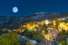 Opinião média de Trikala em Corinth Grécia contra a Lua cheia Um destino turístico bonito Foto de Stock Royalty Free