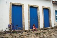Opinião a menina que senta-se na frente das portas azuis fechados em Paraty Imagens de Stock