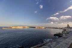 Opinião nas construções históricas da cidade de Valletta, capital de HDR de Malta, com um farol vermelho e branco velho Fotografia de Stock