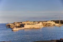Opinião nas construções históricas da cidade de Valletta, capital de HDR de Malta, com um farol vermelho e branco velho Fotografia de Stock Royalty Free