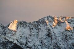 Opinião nevado alpina idílico do pico da corrente de montanha no céu alaranjado do por do sol, cumes julianos, Eslovênia Fotos de Stock Royalty Free
